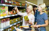 Positive women customers standing near shelves with canned goods at store. Focus on the young woman